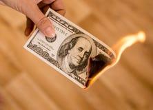 100 долларов ожога в пламенах в руке Стоковые Фото
