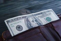 100 долларов счета в старом затрапезном кожаном бумажнике на деревянном tabl Стоковая Фотография