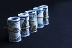 Доллары в кренах на черной предпосылке стоковое изображение rf