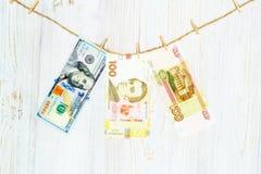 Доллары, hryvnia и рубли приостанавливанные на зажимках для белья Отмывание денег, очковтирательство валюты и концепция коррупции стоковое фото