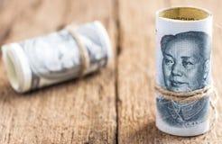 Доллар США против банкноты юаней фарфора на backgro деревянного стола Стоковые Фото