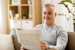 домашнее чтение газеты человека стоковая фотография