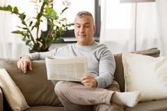 домашнее чтение газеты человека стоковое изображение