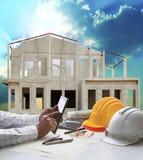 Домашние конструкция и рука держат таблетку на таблице деятельности инженера Стоковая Фотография RF