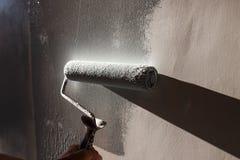 домашние ремонты Красить стены комнаты в сером цвете с роликом краски стоковое изображение