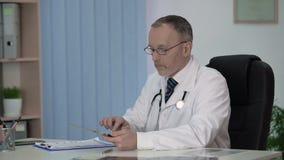 Домашний врач держа электронные медицинские истории, современную медицину акции видеоматериалы