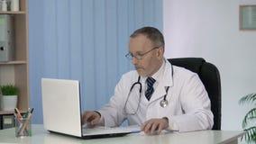 Домашний врач кладя терпеливые данные в электронную медицинскую историю на компьтер-книжку видеоматериал