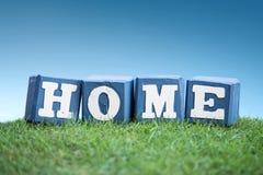 ДОМАШНИЙ знак сделанный из деревянных блоков на траве Стоковая Фотография