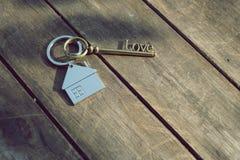 Домашний ключ с кольцом для ключей дома влюбленности на деревянной предпосылке Стоковые Фотографии RF