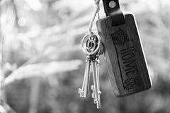 Домашний ключ с смертной казнью через повешение кольца для ключей дома с предпосылкой сада нерезкости Стоковая Фотография