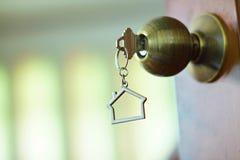 Домашний ключ с keychain в keyhole, концепцией дома свойства Стоковое Изображение