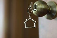 Домашний ключ с keychain в keyhole, концепцией дома свойства Стоковая Фотография