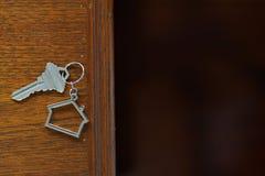 Домашний ключ с keychain на деревянном столе, концепцией дома свойства Стоковые Фото