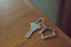 Домашний ключ с keychain на деревянном столе, концепцией дома свойства Стоковое фото RF