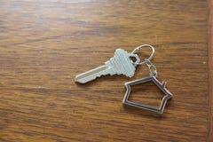 Домашний ключ с keychain на деревянном столе, концепцией дома свойства Стоковые Изображения