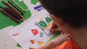 Домашний мальчик рисует с покрашенными карандашами в альбоме акции видеоматериалы