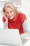 домашний старший компьтер-книжки используя женщину стоковая фотография