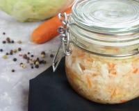 Домашний sauerkraut с салатом в стеклянном опарнике вертикальный взгляд, конец-вверх состав свежих овощей и sauerkraut стоковые изображения