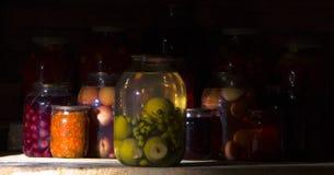 Домашняя консервация в темном погребе в котором выходить несколько лучей света стоковые фотографии rf