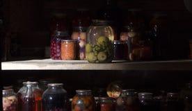 Домашняя консервация в темном погребе в котором выходить несколько лучей света стоковое фото