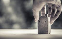 Домашняя модель сделанная от глины на деревянной поверхности, держа правой рукой, запачкала bokeh как предпосылка, банковская ссу Стоковые Фото