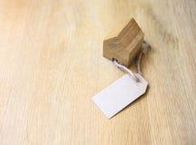 Домашняя модель с бумажной биркой подарка на деревянной недвижимости предпосылки Стоковое Изображение RF