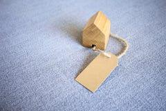 Домашняя модель с бумажной биркой подарка на серой текстурированной предпосылке Стоковая Фотография