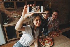 Домашняя партия пиццы Друзья имеют потеху и едят кухню пиццы дома Стоковые Фото
