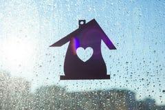 домашняя помадка Домашний символ с формой сердца на предпосылке окна с солнечными падениями дождя Стоковое Изображение