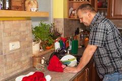 Домашняя работа в кухне Человек моя пакостные блюда в кухонной раковине Отечественный очищать вверх после партии Стоковое Изображение RF