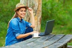 Домашняя работа в саде с компьтер-книжкой и кофейной чашкой Стоковое Изображение RF