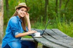 Домашняя работа в саде с компьтер-книжкой и кофейной чашкой Стоковая Фотография