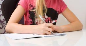 Домашняя работа сочинительства ребенка в книге тренировки Стоковые Изображения