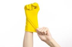Домашняя работа, стирка и чистка темы: рука человека держа желтый цвет и носит резиновые перчатки для очищать изолированные на бе Стоковое Изображение RF