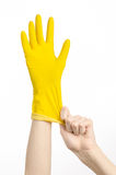 Домашняя работа, стирка и чистка темы: рука человека держа желтый цвет и носит резиновые перчатки для очищать изолированные на бе Стоковые Изображения