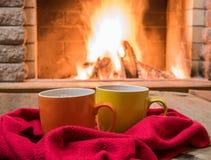 Домашняя сладостная домашняя принципиальная схема 2 кружки чая около уютного камина, Стоковые Фотографии RF