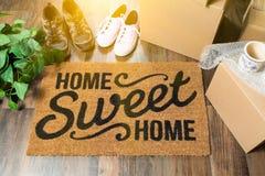 Домашняя сладостная домашняя радушная циновка, Moving коробки, женщины и мужские ботинки стоковые изображения rf