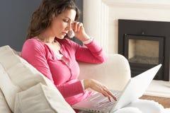 домашняя софа телефона компьтер-книжки используя женщину Стоковое Изображение
