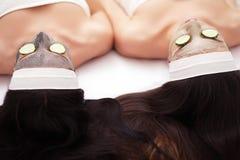 домашняя спа 2 женщины держа части огурца на их сторонах лежа кровать Стоковое Фото