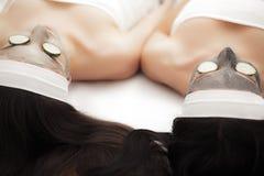 домашняя спа 2 женщины держа части огурца на их сторонах ly Стоковые Изображения