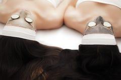 домашняя спа 2 женщины держа части огурца на их сторонах ly Стоковые Фотографии RF
