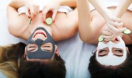 домашняя спа 2 женщины держа части огурца на их сторонах ly Стоковое Фото