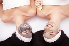 домашняя спа 2 красивых молодой женщины держа части огурца на их глазах и усмехаясь пока на кровати Стоковое Изображение RF