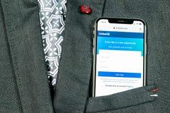 Домашняя страница Linkedin на конце-вверх экрана iPhone x Яблока в карманн куртки Значок Linkedin app Linkedin com Социальные сре стоковые изображения