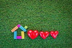 Домашняя сладостная домашняя концепция с домашней моделью и 3 красными сердцами дальше Стоковое Фото