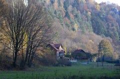 Дома в лесе с деревьями в Ojcow, Польше, 10 29 2005 Стоковые Изображения