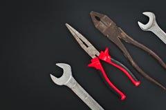 Дома использовать плоскогубцы комбинации ручных резцов, плоскогубцы носа иглы, ключ на черной предпосылке Стоковая Фотография RF