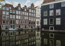 Дома канала вдоль соединения каналов Oudezijds Voorburgwal и Oudezijds Achterburgwal Стоковые Изображения RF