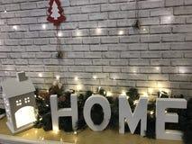 ` ДОМА ` надписи состоит из больших белых пластичных декоративных писем, дома малой игрушки светящего на фоне Стоковые Фото