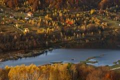 Дома на берегах озера в покрашенных древесинах Стоковые Фото